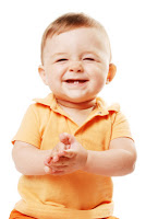 Baby-in-orange-shirt-with-two-teeth-smiling